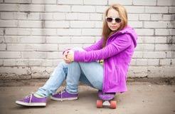 La muchacha rubia hermosa en gafas de sol se sienta en el monopatín Foto de archivo