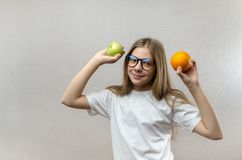 La muchacha rubia hermosa en una camiseta blanca sonr?e y sostiene una manzana y una naranja en sus manos Nutrici?n sana para fotos de archivo libres de regalías