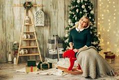 La muchacha rubia hermosa es abre el regalo en la Navidad Fotografía de archivo libre de regalías