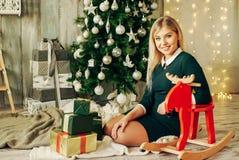 La muchacha rubia hermosa es abre el regalo en la Navidad Foto de archivo