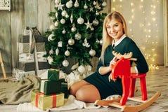 La muchacha rubia hermosa es abre el regalo en la Navidad Fotos de archivo libres de regalías