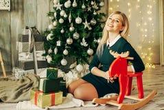 La muchacha rubia hermosa es abre el regalo en la Navidad Imagen de archivo libre de regalías