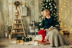 La muchacha rubia hermosa es abre el regalo en la Navidad Foto de archivo libre de regalías