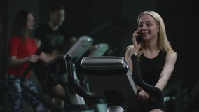 La muchacha rubia hermosa es trabajo diligente en una bicicleta estática y el hablar con su teléfono en un fondo de practicado almacen de video