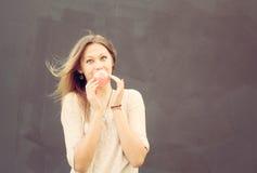 La muchacha rubia hermosa infla una burbuja roja del chicle outdoor Fotos de archivo