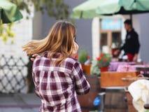La muchacha rubia hermosa joven comunica en un smartphone en la calle de la ciudad vieja Artilugios en la comunicación diaria nue fotografía de archivo
