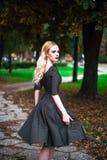 La muchacha rubia hermosa joven con el lápiz labial rojo en sus ojos brillantes grandes y lo hace en el vestido que presenta en l Foto de archivo