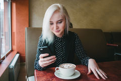 La muchacha rubia hermosa joven mira en el teléfono que se sienta en un café Café con las melcochas para el desayuno Foto de archivo libre de regalías