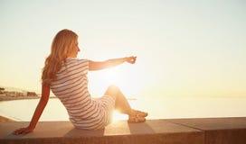 La muchacha rubia hermosa joven se sienta en la playa y disfruta del sunr foto de archivo