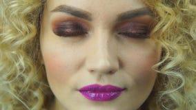 La muchacha rubia hermosa la abre los ojos y sonrisa con los labios rosados metrajes