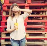 La muchacha rubia hermosa la cierra los soportes de los ojos cerca de los estantes de madera outdoor Fotos de archivo libres de regalías