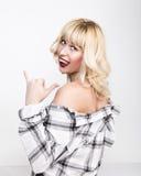 La muchacha rubia hermosa que lleva una camisa de tela escocesa que muestra la lengua y los fingeres hace la muestra de Shaka Foto de archivo libre de regalías