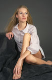 La muchacha rubia hermosa que se sienta en una alfombra Fotos de archivo