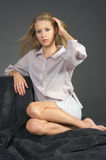 La muchacha rubia hermosa que se sienta en una alfombra Imagen de archivo libre de regalías