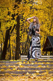 La muchacha rubia hermosa se coloca en un fondo de hojas amarillas del otoño Foto de archivo