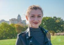 La muchacha rubia hermosa se coloca y sonríe en el fondo verde del césped Fotos de archivo libres de regalías