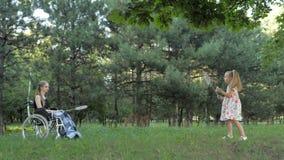 La muchacha rubia hermosa se está sentando en silla de ruedas y se está divirtiendo jugando a bádminton almacen de video