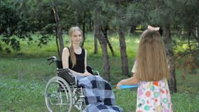 La muchacha rubia hermosa se está sentando en silla de ruedas y se está divirtiendo jugando y lanzando el disco volador metrajes