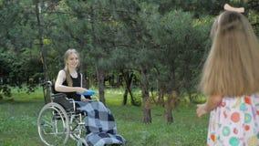 La muchacha rubia hermosa se está sentando en silla de ruedas y se está divirtiendo jugando y lanzando el disco volador almacen de metraje de vídeo