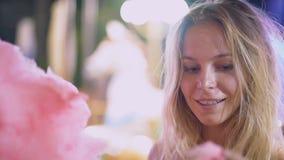 La muchacha rubia joven atractiva con algodón dulce monta en un carrusel y sonríe baile y el engañar alrededor lento almacen de metraje de vídeo