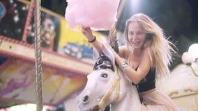 La muchacha rubia joven atractiva con algodón dulce monta en un carrusel y sonríe baile y el engañar alrededor lento metrajes
