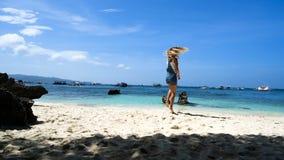 La muchacha rubia joven corre a lo largo de la playa blanca con las rocas y la sonrisa I no dude en metrajes