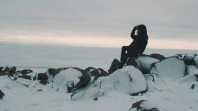 La muchacha rubia joven en chaqueta y casquillo negros se sienta en piedras delante del mar congelado almacen de metraje de vídeo