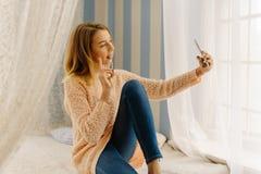 La muchacha rubia joven está haciendo que el pedazo firma y está tomando el selfie usando el teléfono móvil El retrato lateral Fotografía de archivo