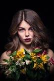 La muchacha rubia joven guarda las flores en fondo negro Fotos de archivo libres de regalías
