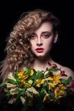 La muchacha rubia joven guarda las flores en fondo negro Imagen de archivo