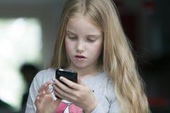 La muchacha rubia joven mira el teléfono móvil fotos de archivo libres de regalías
