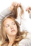 La muchacha rubia joven mira su pelo Fotografía de archivo