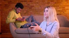 La muchacha rubia juega el videojuego en piso atento con su novio africano que trabaja con smartphone en fondo almacen de metraje de vídeo