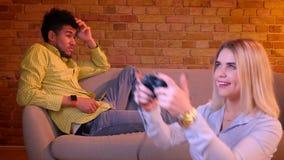 La muchacha rubia juega el videojuego en piso atento y el novio africano que siente deprimido y solo en fondo almacen de video