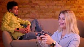 La muchacha rubia juega el videojuego en piso atento y el novio africano que siente triste y solo en fondo almacen de video