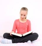 La muchacha rubia lee el libro interesante que se sienta en cama Foto de archivo libre de regalías