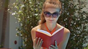La muchacha rubia lee el libro rojo por la opinión del cierre de la planta tropical