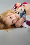La muchacha rubia linda abraza su muñeca Fotos de archivo