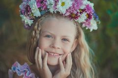 La muchacha rubia linda con los ojos azules cierra el retrato que lleva las flores salvajes enrruella en la cabeza superior que s Foto de archivo