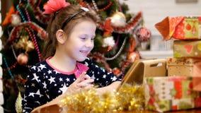 La muchacha rubia linda, con un arco rosado en su pelo, en un vestido hermoso está mirando algo en una tableta, cerca de presente almacen de video