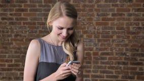 La muchacha rubia linda joven está mirando las fotos en el smartphone, mostrándolo, sonriendo, concepto de la comunicación, fondo almacen de video