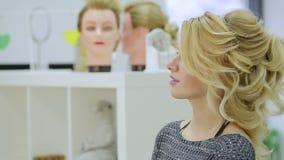 La muchacha rubia linda mira en el espejo el salón de belleza almacen de metraje de vídeo