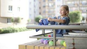 La muchacha rubia linda sacude apagado pantalones cortos del bebé en el balcón en verano almacen de metraje de vídeo