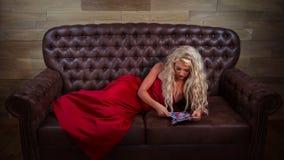 La muchacha rubia miente en el sofá de cuero imágenes de archivo libres de regalías
