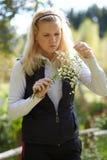La muchacha rubia mira el ramo de margaritas Foto de archivo libre de regalías
