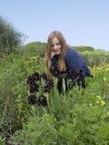 La muchacha rubia mira las flores irisa en el área natural protegida Fotos de archivo libres de regalías