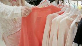 La muchacha rubia natural atractiva joven hace la blusa de las compras en el boutique, gran tienda de la felicidad de las cosas d almacen de metraje de vídeo
