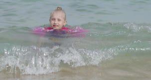 La muchacha rubia preciosa es flotante o que nada en el mar almacen de metraje de vídeo