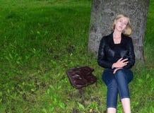 La muchacha rubia que se sienta cerca del árbol con un teléfono foto de archivo libre de regalías