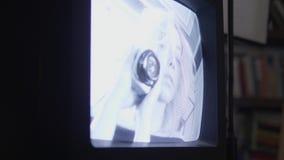 La muchacha rubia que sostiene la cámara de seguridad aparece en la exhibición de la TV vieja, cámara lenta almacen de metraje de vídeo